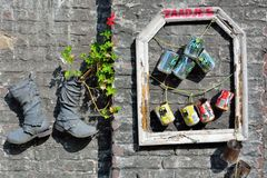 Recycled  boots and cans  used as a planter. Hanging against a wall Royalty Free Stock Photo