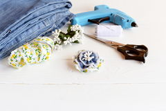Recycled jeans brooch. Pretty flower brooch using recycled old jeans. Craft idea for children and women. Easy home made denim accessory. Scissors, glue gun, lace Stock Photography