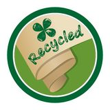 Recycled material emblem, rolled old yellowed paper in circle shape, inscription recycled and green cloverleaf motif with chipped Stock Images