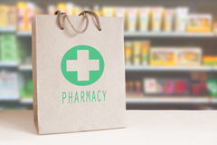Recycled paper bag with a green Pharmacy logo in a drugstore. Empty copy space