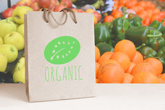 Recycled paper bag with the ORGANIC word and logo. Some natural fruits and vegetables. Empty copy space Stock Images