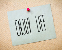 Recycled paper note pinned on cork board.Enjoy Life Message.Happiness Concept Stock Photos