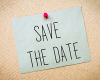 Recycled paper note pinned on cork board.Save the Date Message