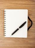 Recycled paper notebook with black elastic band and pen Stock Photo