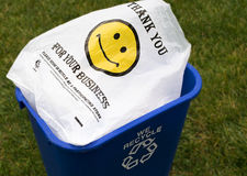 Recycled Plastic Bag  Happy Face. Plastic bag with a happy face is shown in a recycle bin Royalty Free Stock Photo