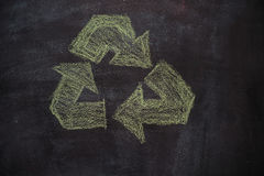 Recycled symbol on black chalkboard. Green recycled symbol drawn with chalk on blackboard Royalty Free Stock Photo