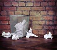 Recycleer bak die met verfrommelde documenten wordt gevuld. Bakstenen muurachtergrond stock fotografie