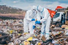 Recyclerende arbeiders die op de stortplaats onderzoeken Stock Afbeelding