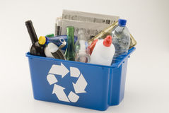 Recycling. Blue recycling bin full of household materials including metal plastic glass paper and cardboard. White background Stock Photos