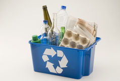 Recycling. Blue recycling bin full of household materials including plastic glass paper and cardboard. White background Royalty Free Stock Image