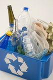Recycling. Blue recycling bin full of household materials including metal plastic glass paper and cardboard. White background Stock Photo