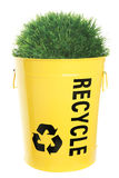 Recycling. Concept. Green grass growing out of recycle bin, showing the recyle sign / icon. Yellow  bucket isolated on white Stock Image
