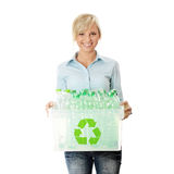 Recycling. Young woman carrying a plastic container full with empty recyclable household material. Recycling concept Stock Photos