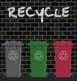 Recycling. Wheelie bins against a brick wall Royalty Free Stock Images