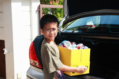 Recycling. A boy doing his part of recycling by collecting aluminium cans and put them into a paper box, getting ready to go to a recycling centre. A method of Stock Photo