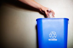 Recycling. Woman's arm dropping plastic bottling into recycling container Royalty Free Stock Photo