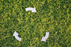 Recycling Arrows on Green Grass Stock Photos