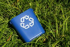 Recycling bin in bushes. Recycle and save the earth and trees stock photo