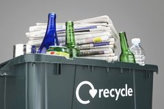 Recycling bin filled with waste paper and bottles close-up Royalty Free Stock Image