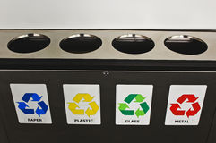 Recycling bins. Metal recycling bin in at the wall in a public place for paper, plastic, glass and metal Royalty Free Stock Photos