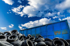 Recycling business, container and tires. Recycling business with metal container and car tires over blue sky. Ecology and recycle industry, saving nature and royalty free stock photo