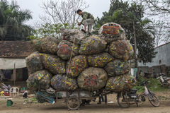 Recycling cans and bottles loaded on cart behind motorbike. Stock Image