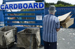 Recycling Center. Man throwing cardboard waste in recycling and disposal center Royalty Free Stock Image