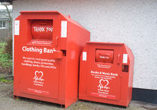 Recycling for charity. Recycling units one for clothing and one for books and CDs. Donations help to raise funds for the British Heart Foundation Stock Photo