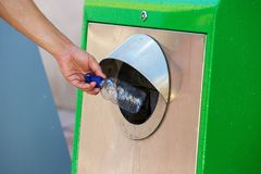 Recycling. Close up male hand throwing away plastic bottle in recycling bin Stock Images