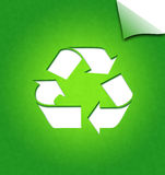 Recycling concept. Recycling symbol on green paper with page curl Stock Image