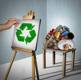 Recycling Concept. As a pile of recyclable trash as plastic,metal and paper with a creative environmentalist painting a recycle symbol on a canvas with 3D Royalty Free Stock Image