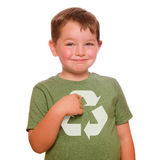 Recycling concept with child. Recycling for the future concept with smiling child proudly pointing at recycling logo on his green t-shirt royalty free stock image