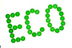 Recycling concept with Eco caption made of green plastic bottle caps. Pattern green on white royalty free stock photos