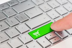 A finger press a green key with Shopping cart icon symbol on laptop keyboard. stock photos