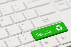 A green key with recycle icon symbol on white laptop keyboard. Recycling concept: A green key with recycle icon symbol on white laptop keyboard Stock Photos