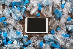 Recycling concept. Tablet wooden background around the transparent plastic bottles. The problem of ecology, environmental pollutio. N Royalty Free Stock Photo