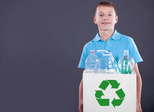 Recycling concept with young boy carrying recycling bin Royalty Free Stock Image