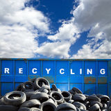Recycling container and tires. Recycling container and car tires over blue sky royalty free stock photo