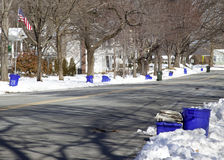 Recycling Day--Cans Lined up on Street. Recycling day in a suburban neighborhood, with blue recycling cans lined up along side of street in front of houses Royalty Free Stock Photos