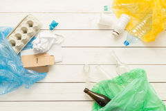 Recycling and ecology - sorting waste into bags. Recycling and ecology. Sorting segregating household waste paper, glass, plastic into bags captured from above Stock Image