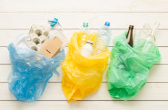Recycling and ecology - sorting waste into bags. Recycling and ecology. Sorting segregating household waste paper, glass, plastic into bags captured from above Stock Photos