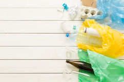 Recycling and ecology - sorting waste into bags. Recycling and ecology. Sorting segregating household waste paper, glass, plastic into bags captured from above Royalty Free Stock Photo