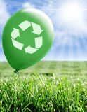 Recycling environmental scene. Green balloon with recycle symbol over field of grass Royalty Free Stock Photography
