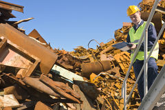 Recycling expert. Standing on a metal staircase in front of a steel scrap heap stock images