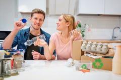 recycling Família nova ciente que classifica garrafas e tampas plásticas vazias ao sentar-se na tabela com o outro desperdício em fotos de stock royalty free
