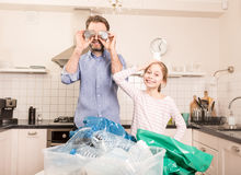 Recycling - family having fun while sorting waste. Recycling and ecology - happy caucasian family father and daughter having fun while sorting segregating royalty free stock photo