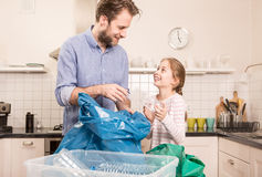 Recycling - family sorting segregating household waste. Recycling and ecology - happy caucasian family father and daughter sorting segregating household waste in stock images