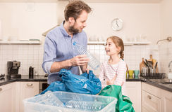 Recycling - family sorting segregating household waste. Recycling and ecology - happy caucasian family father and daughter sorting segregating household waste in stock photo