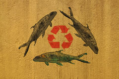 Recycling for the fishes. A composition of an stained wall image nd fishes stock photo