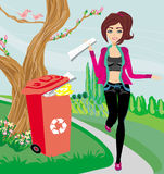 Recycling - girl throws paper into red bin Stock Image